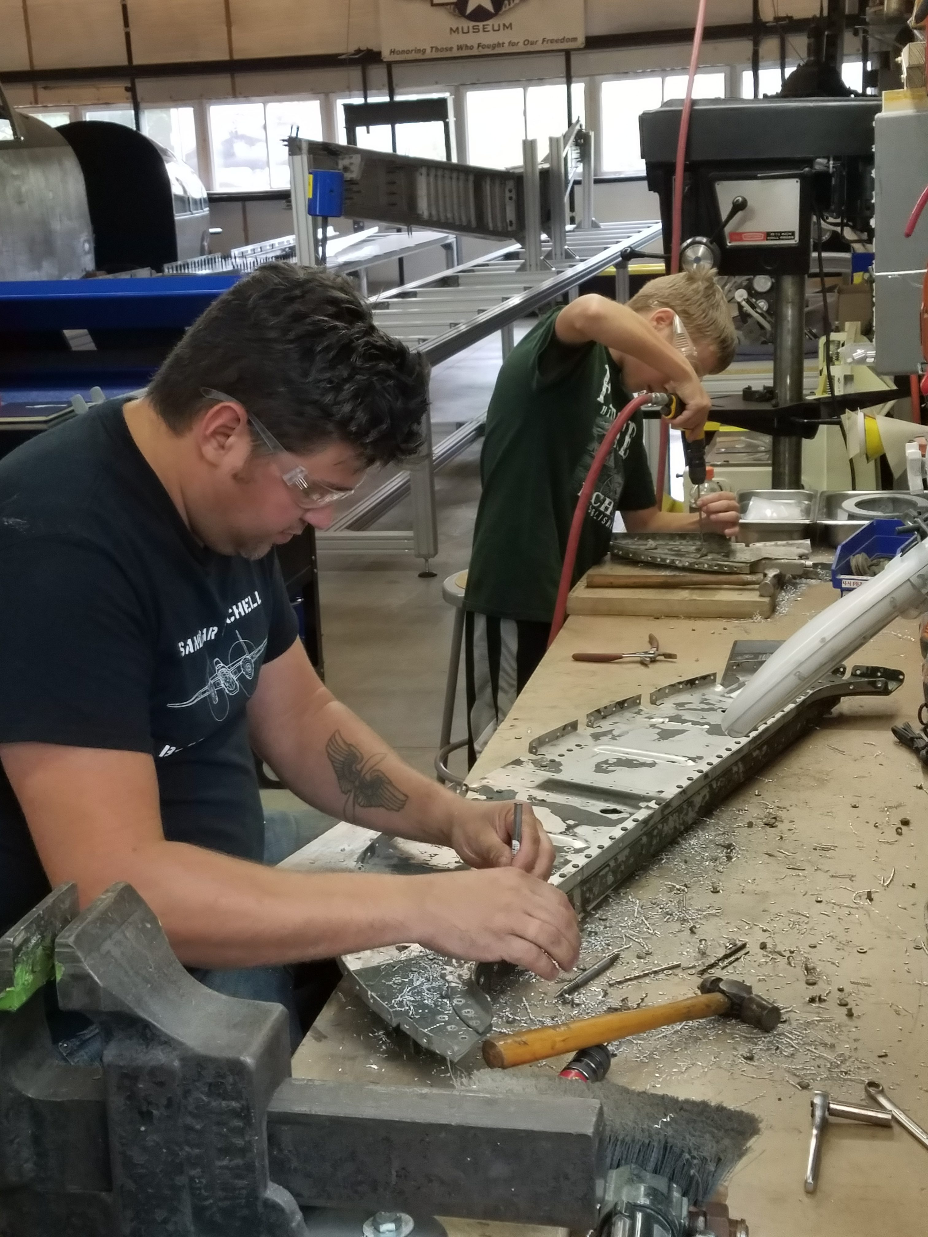 Founder Patrick Mihalek and youth Matt drilling rivets from B-25 parts.