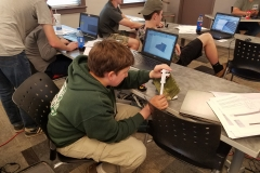 Joel measuring a B-25 part to create a CAD model in SolidWorks during CAD training class.