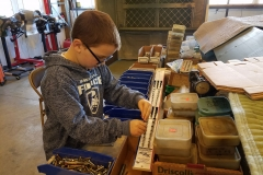 Nolan, who is a part of the museum's youth mentoring program, learns about hardware fasteners by sorting nuts and bolts donated to the Warbirds of Glory Museum.